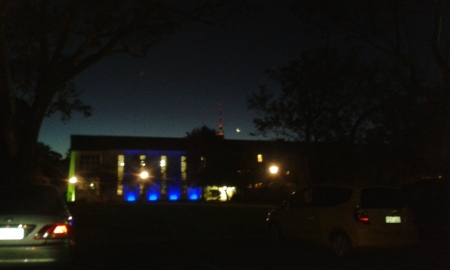 In the foreground, University House decorates its frontage with rich bright blue
