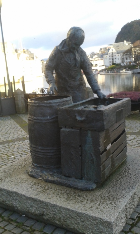 Bronze (?) statue of a fishwife at Alesund - where there are complex waterways.